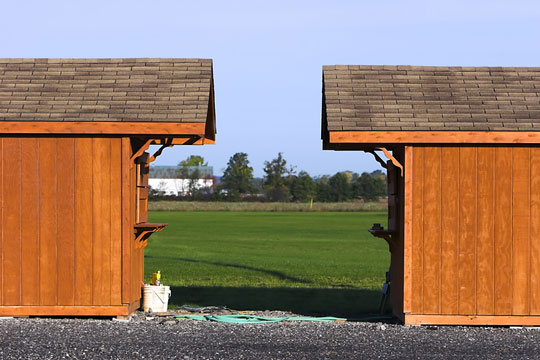 two wooden storage sheds